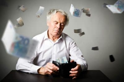 Retired man emptying wallet, bills flying through air