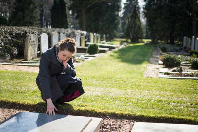 woman kneeling at graveside