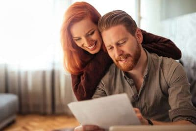 young couple happily reviewing paperwork