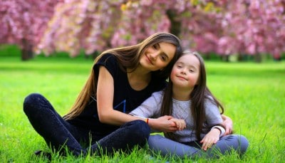 Young lady sitting in a park with a special needs child