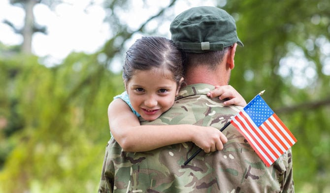 Back view of soldier with flag and daughter