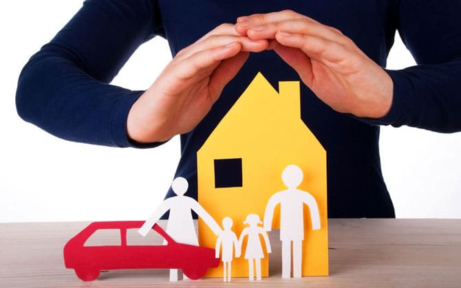 hands covering paper house and family