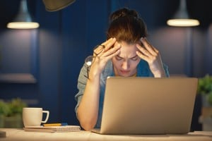 Stressed female business owner working at laptop