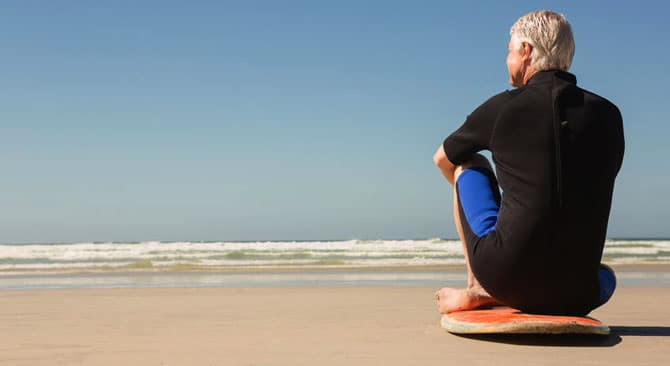 Rear view of senior man sitting on surfboard at beach on sunny day
