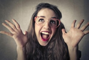Young woman with big glasses and bright red lipstick and surprised look