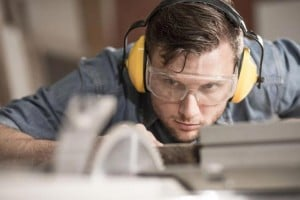arpenter while using electric tools wearing protective headphones