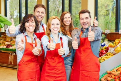 Happy staff in red aprons in greocery store