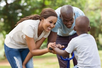 Happy african parents in park with child on bicycle