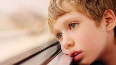 Lonely little boy looking out window