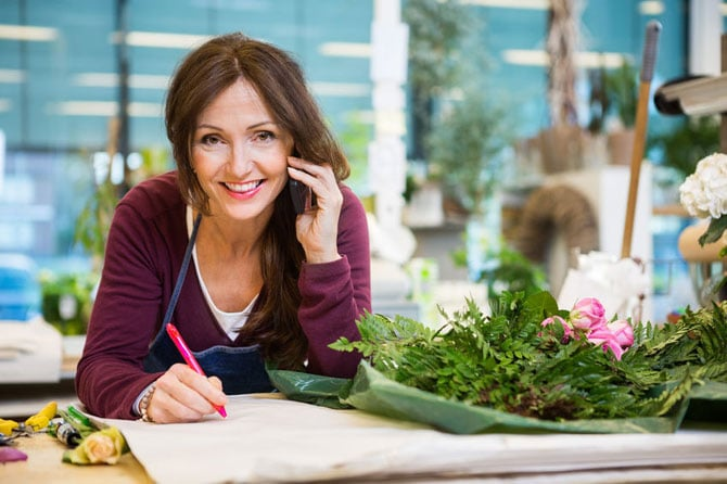 Happy female florist using mobile phone while writing on paper