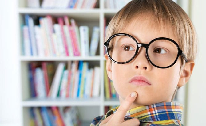 Little boy in glasses with questioning look on face