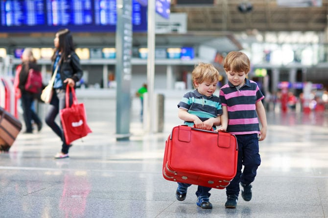 Two little boys carrying a red suitcase in airport