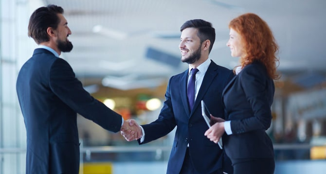 Three business people in dark suits, shaking hands