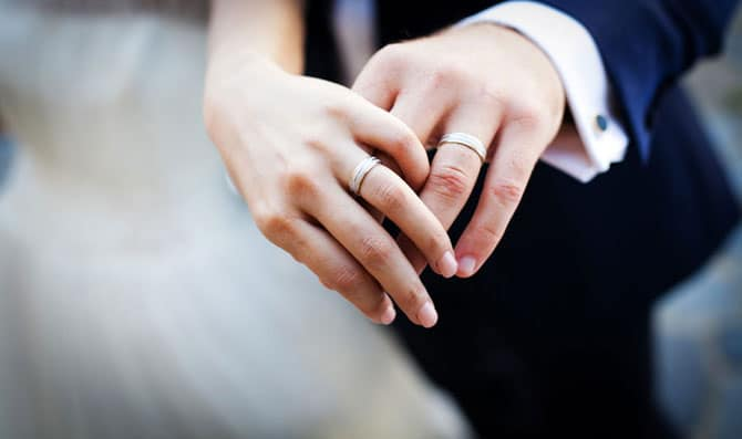 hands of bride and groom wearing wedding rings