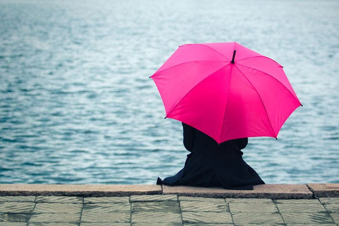 Lady in black coat holding pink umbrella by the sea