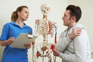 Man in doctor's office with mediacal assistant, skeleton in background