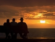 Seniors on a bench at the beach facing the sunset