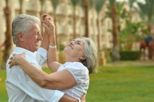 Happy retired couple dancing, palm trees in background