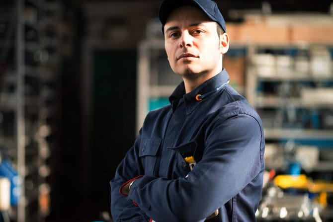 Mechanic in blue uniform and cap, arms crossed