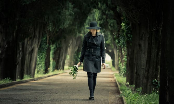 Woman in black outfit walking on wooded lane, holding flowers
