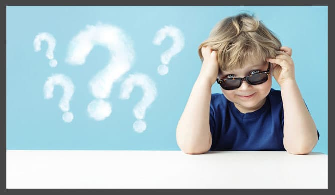 Little kid in sunglasses with question marks in background
