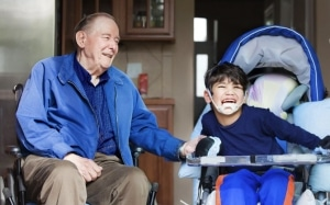 Special needs child with grandfather in wheelchair
