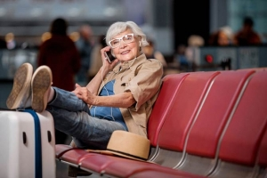 Senior woman happily talking on cell phone, seated at airpot