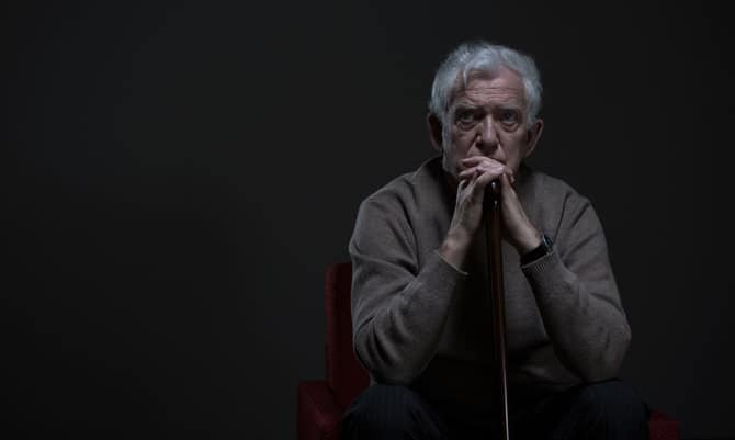 Troubled, aging man seted in dark room with cane
