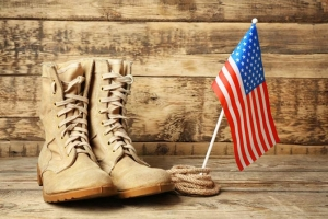 Pair of army boots on wood floor, small american flag off to the side