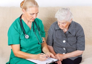 Aging woman reviewing paperwork with female medical staff