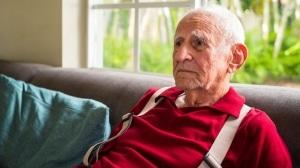 Aging gentelman in red shirt on sofa