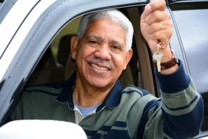 smiling older gentleman in car, holding keys out the window
