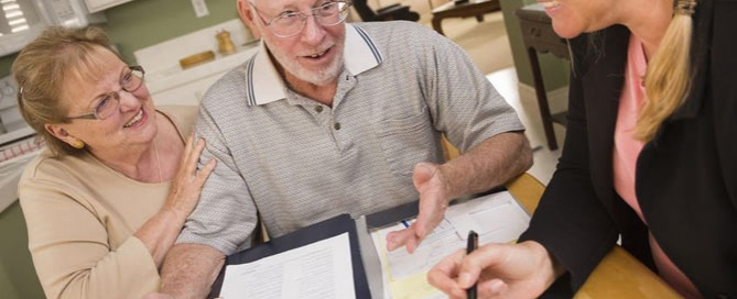 Older couple reviewing documents at kitchen table with professional woman