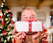 Man holding wrapped gift, christmas tree in background