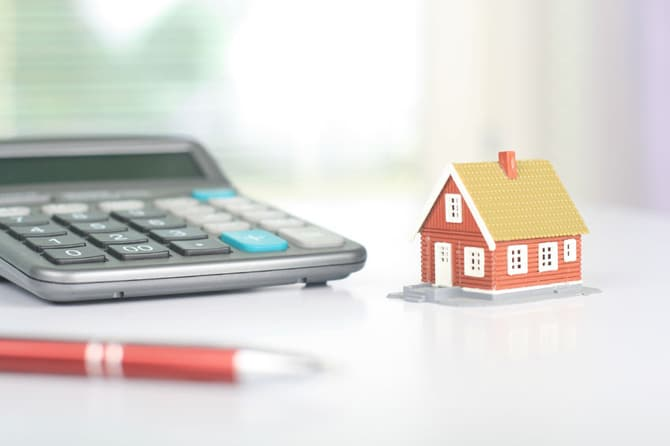 Picture of calsimple culator and miniature house.