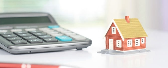Calculator and pen with tiny model of house