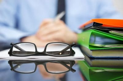 reading glasses and file folders on desk, with professional sitting behind
