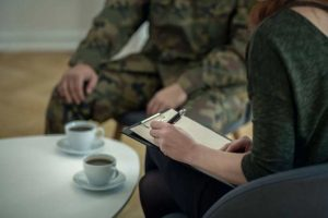 Soldier having coffee with someone filling out paperwork