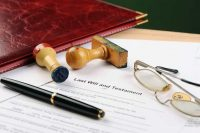 Estate planning document, pen, glasses and stamp